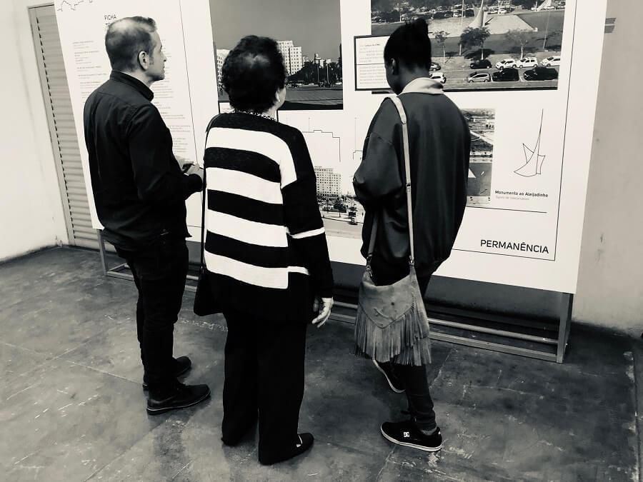 Um homem moreno claro, uma jovem negra e uma senhora idosa branca olham a exposição.