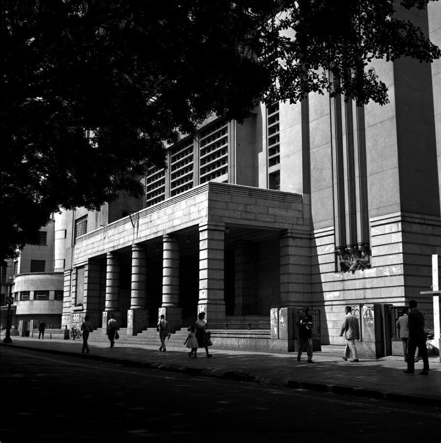 Fachada de um edifício massudo e grande, com pessoas andando na rua à frente.