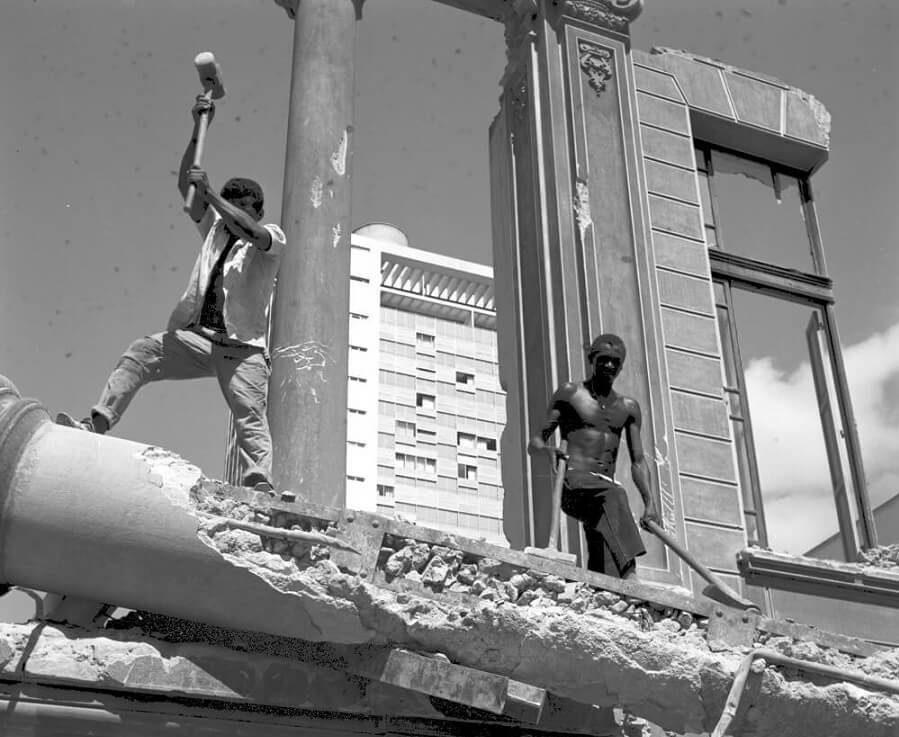 Dois homens trabalhando na demolição de uma coluna, em um canteiro de demolição.