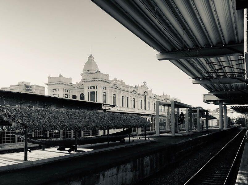Trilhos da Estação Central do metrô, com objetos expostos ao lado do trilho, pertencentes ao Museu de Artes e Ofícios. Ao fundo aparece a edificação do museu.