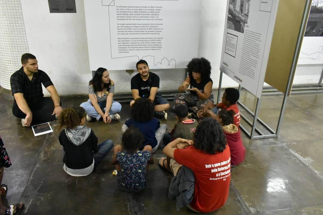 Uma roda de jovens conversam sentados no chão, na exposição no Metrô de BH.