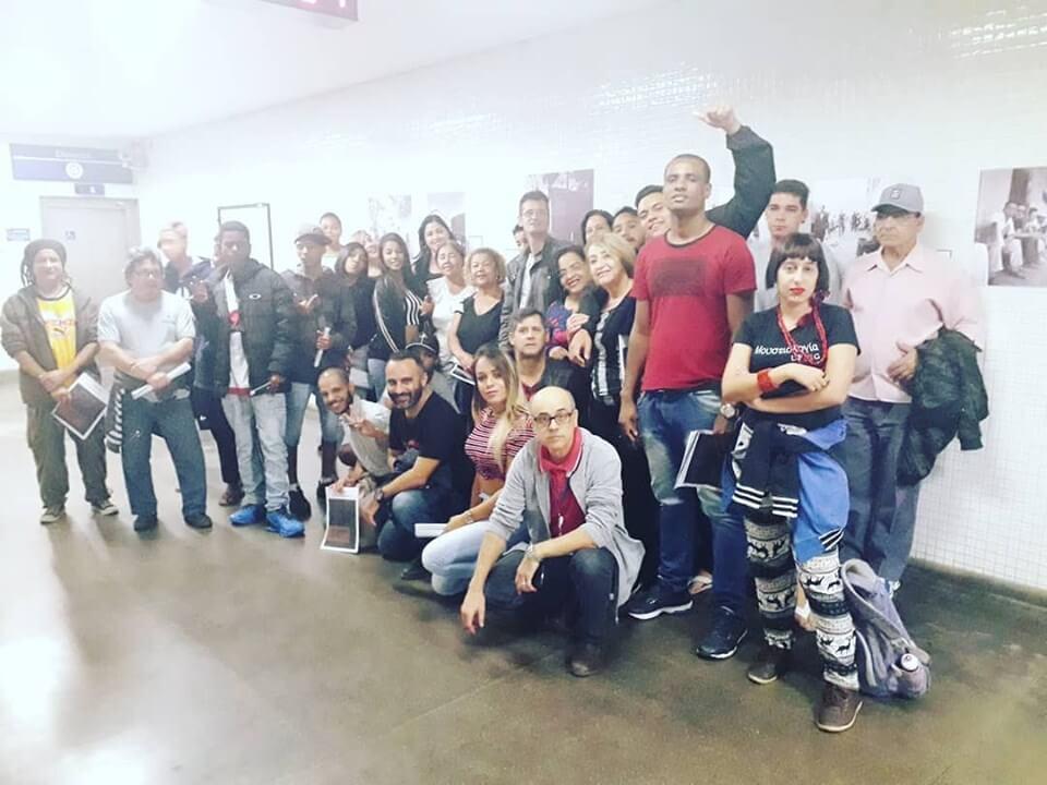 Um grupo de pessoas sorri para a foto na exposição no metrô de BH.